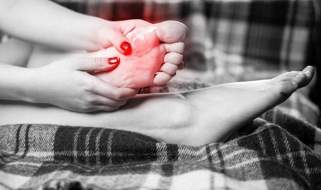 Dor no pé, menina coloca as mãos nos pés, massagem nos pés Foto Premium