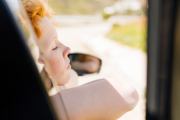 Dormindo feminino na janela do carro Foto gratuita