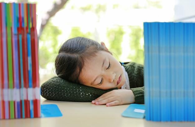 Dormindo menina asiática criança pequena na estante da biblioteca Foto Premium