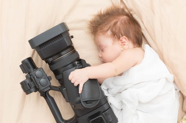 Dormindo menina recém-nascida segurando uma câmera de vídeo. Foto Premium