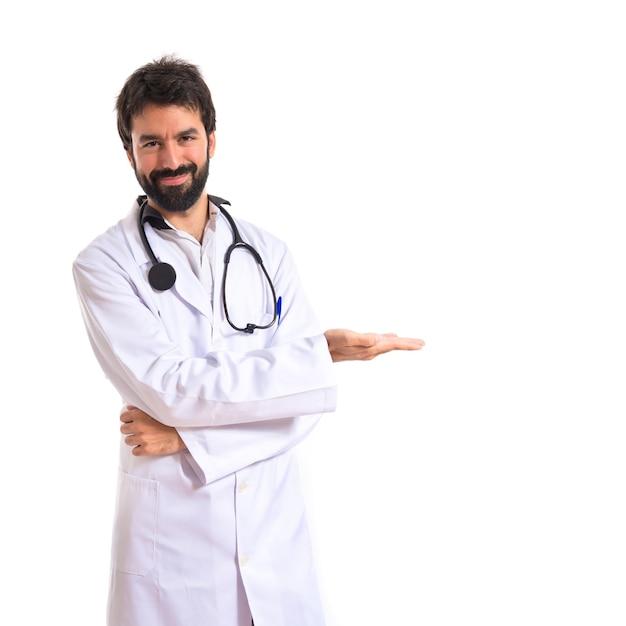 Doutor apresentando algo sobre fundo branco isolado Foto gratuita