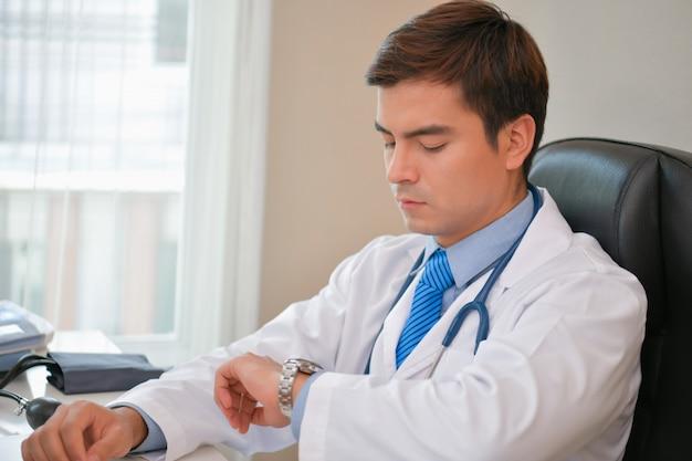Doutor de sorriso que levanta no escritório, está vestindo um estetoscópio. Foto Premium