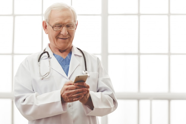 Doutor em jaleco branco médico está usando um smartphone. Foto Premium