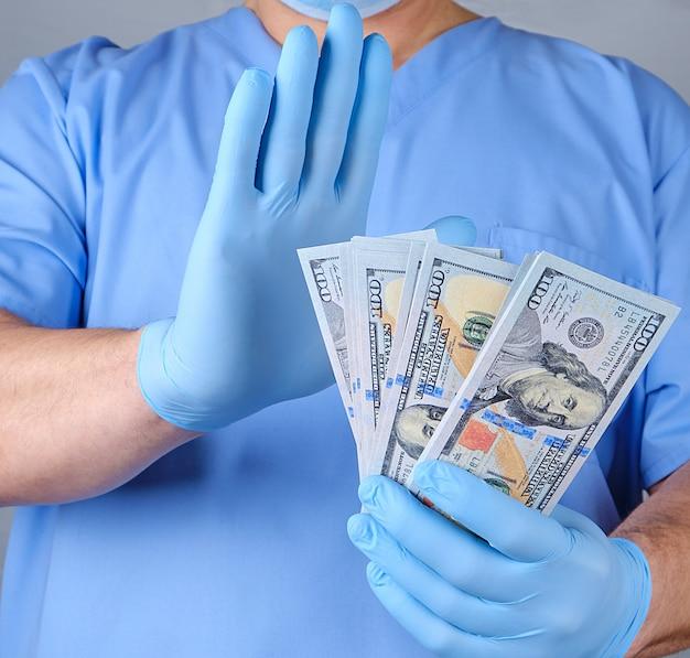 Doutor em luvas de uniforme azul e datex detém um monte de papel-moeda Foto Premium