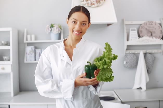 Doutor em uma cozinha com legumes Foto gratuita