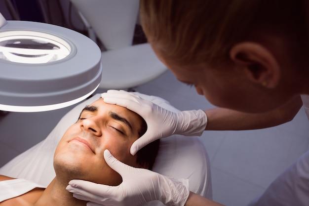 Doutor examinando o rosto do homem para tratamento cosmético Foto gratuita