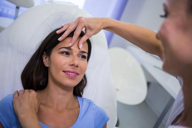 Doutor examinando pacientes do sexo feminino enfrenta na clínica Foto gratuita