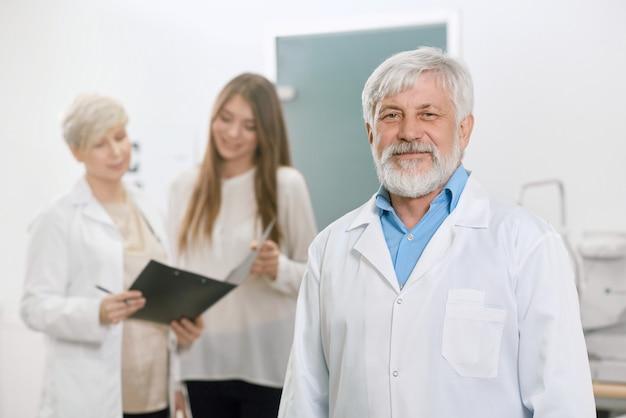 Doutor idoso seguro que fica na frente do assistente e do paciente. Foto Premium