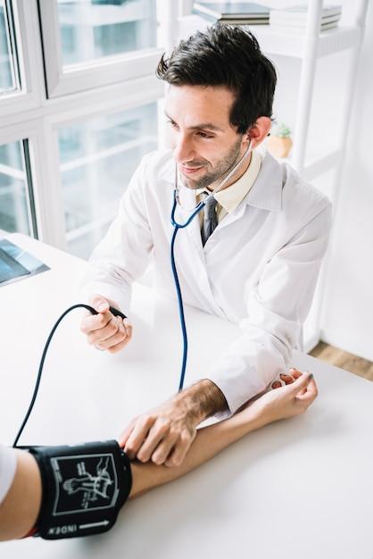 Doutor masculino, medindo, paciente, sangue, pressão, com, estetoscópio Foto gratuita