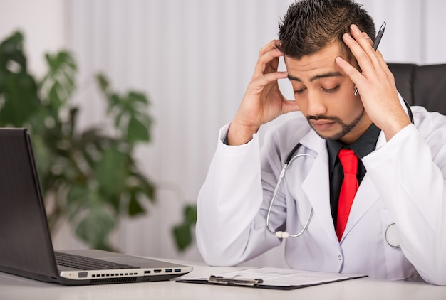 Doutor masculino no jaleco sentado na clínica. Foto Premium