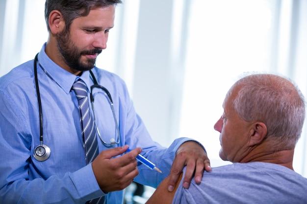 Doutor masculino que dá uma injeção a um paciente Foto gratuita