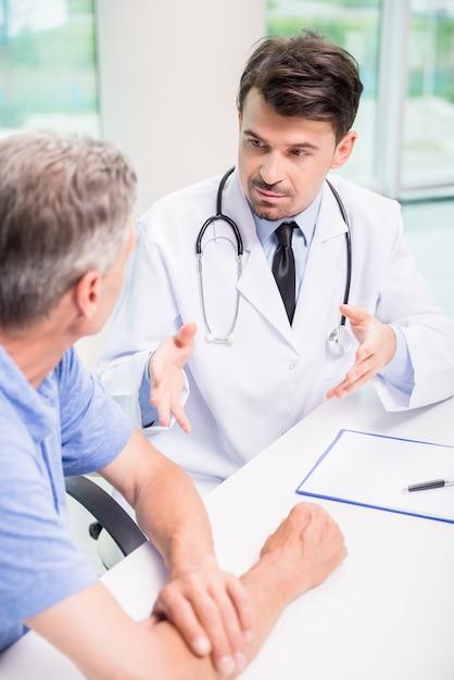 Doutor masculino que fala com o paciente seriamente na clínica. Foto Premium