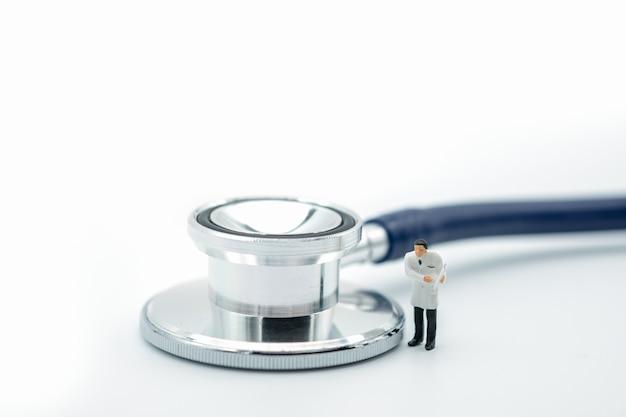 Doutor miniatura figura em pé com estetoscópio Foto Premium