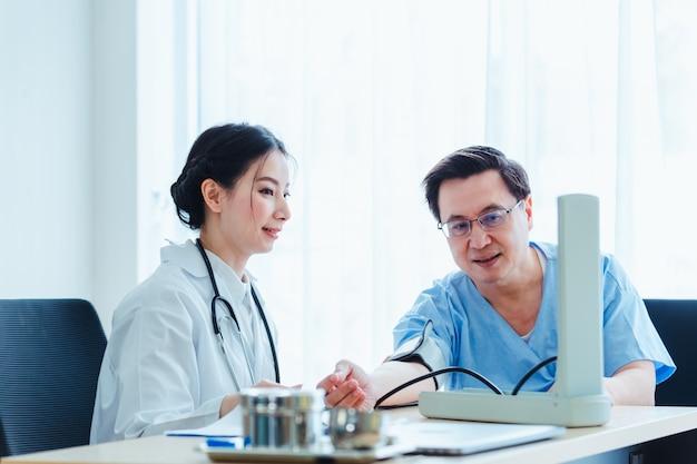 Doutor, mulheres, medindo, sangue, em, paciente, homens, falando, com, médico, em, clínica, escritório Foto Premium