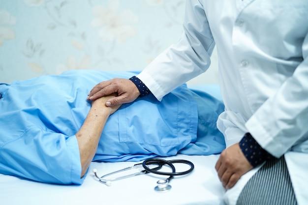 Doutor que guarda as mãos tocantes paciente superior ou idoso asiático da mulher da senhora idosa com amor, cuidado. Foto Premium