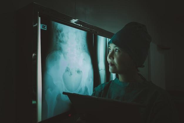 Doutor que olha o filme de raio x abdominal paciente no departamento da radiologia no hospital. Foto Premium