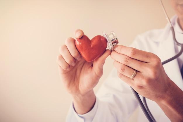 Doutor, segurando, coração vermelho, com, estetoscópio, saúde coração, conceito seguro saúde Foto Premium