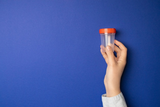 Doutor segurando o copo de amostra. exame médico para a urina no hospital. Foto Premium