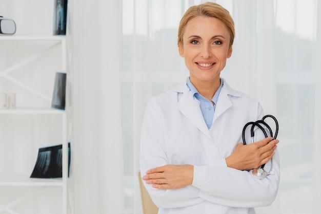 Doutor, segurando o estetoscópio no braço, olhando para a câmera Foto gratuita