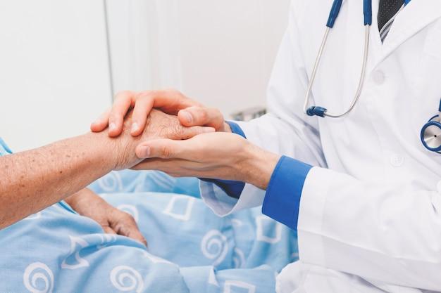 Doutor, segurando, pessoa idosa, mão, com, cuidado, em, hospital.healthcare, e, medicina Foto Premium