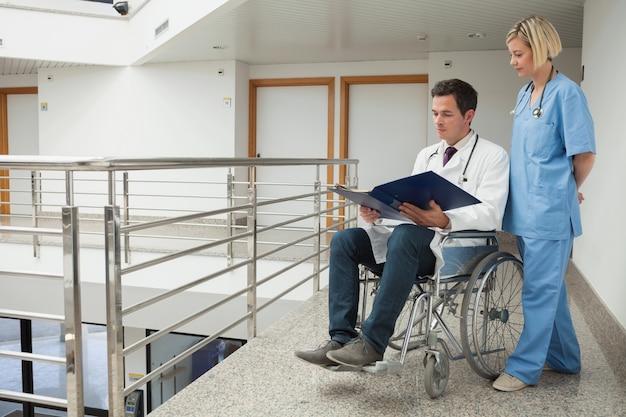 Doutor sentado em cadeira de rodas examinando notas com enfermeira Foto Premium