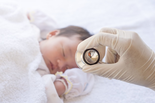 Doutor, usando, estetoscópio, verificar, batida coração, bebê recém-nascido Foto Premium