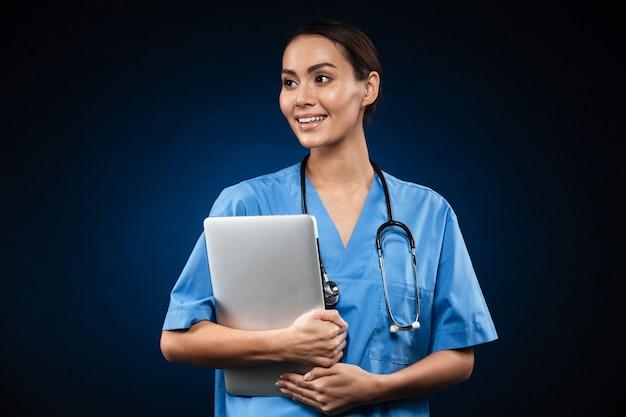 Doutora bonita com computador portátil, olhando de lado Foto gratuita