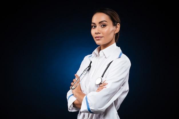 Doutora confiante jovem em vestido médico olhando Foto gratuita