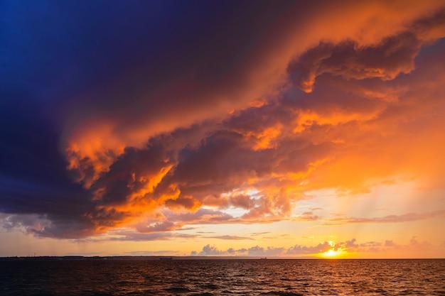 Dramático pôr do sol através de um céu escuro e nublado sobre o oceano. Foto Premium