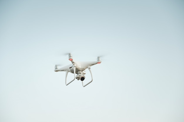 Drone branco pairando em um céu azul brilhante Foto gratuita