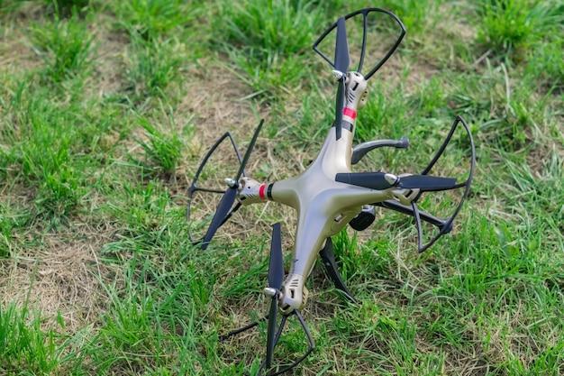 Drone caído na grama verde após a desconexão do controle remoto Foto Premium