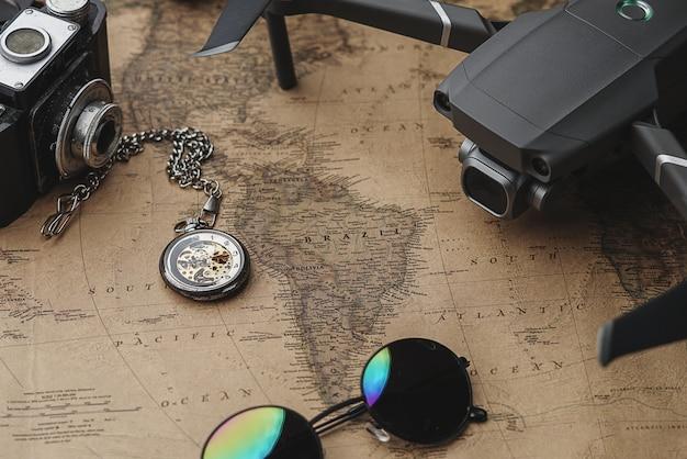 Drone entre acessórios do viajante no mapa antigo vintage Foto Premium