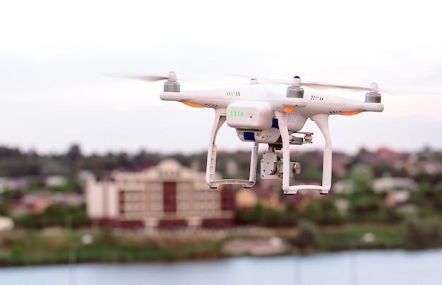 Drone quad helicóptero com câmera digital de alta resolução voando pairando sobre a cidade Foto Premium