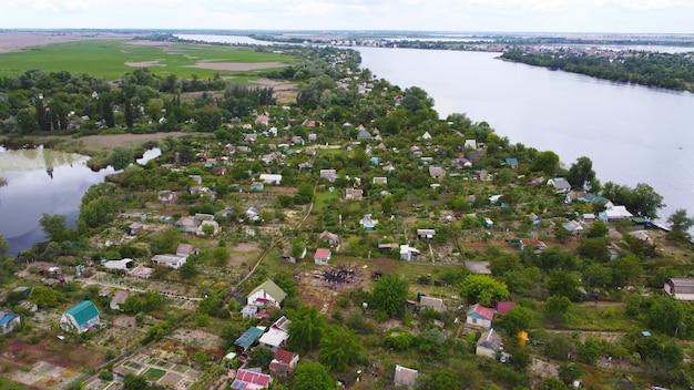 Drone sobrevoa um rio ondulante de cor azul cercado por uma vila local com vários edifícios Foto Premium