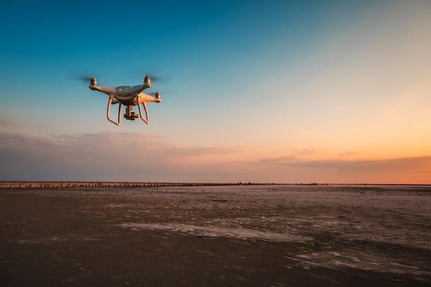 Drone voador em um fundo do pôr do sol do mar Foto Premium