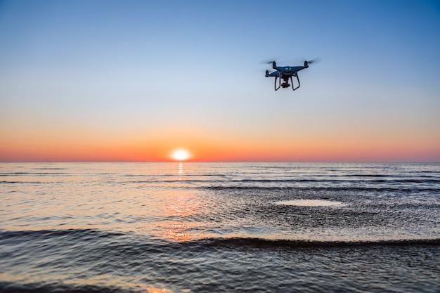 Drone voando em um fundo por do sol do mar Foto Premium