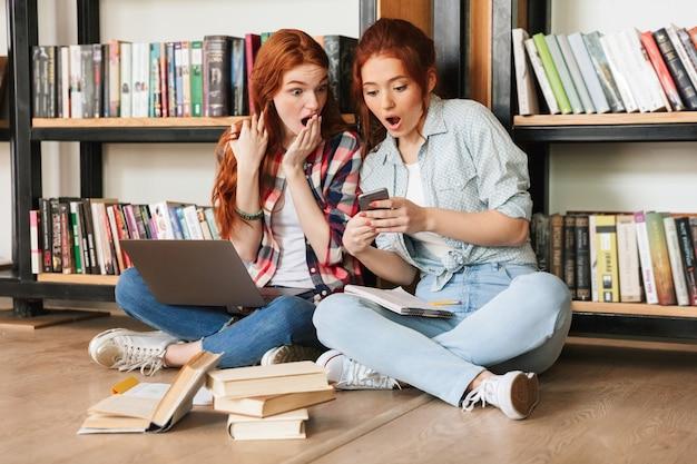 Duas adolescentes chocadas sentadas no chão Foto Premium
