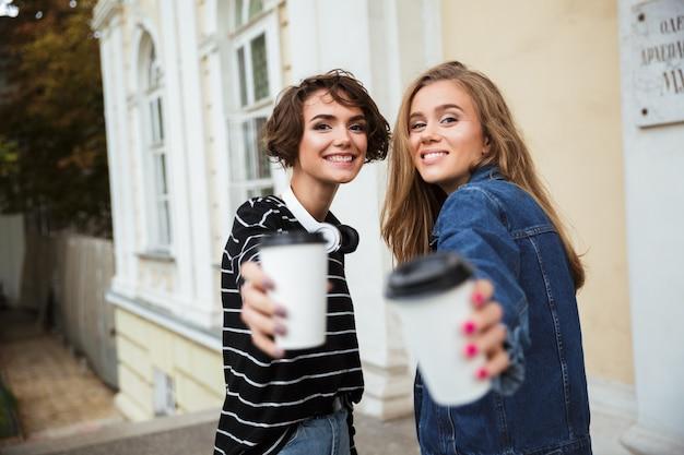 Duas adolescentes sorridentes em óculos de sol brindando Foto gratuita
