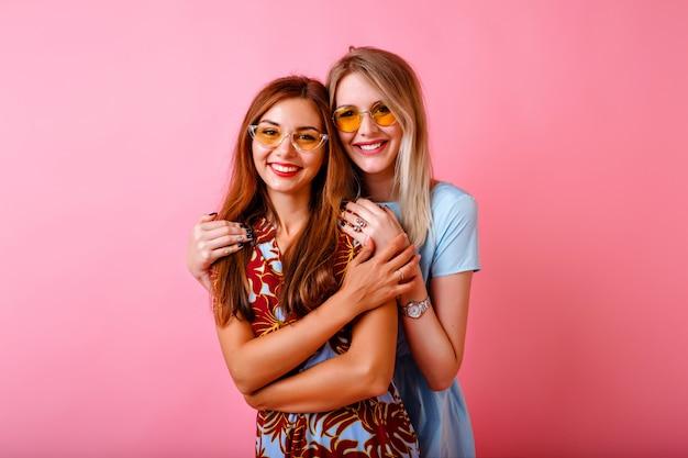 Duas adoráveis mulheres jovens e felizes se divertindo juntas Foto gratuita