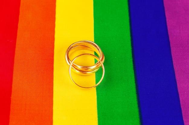Duas alianças de ouro na bandeira do arco-íris lgbt. Foto Premium