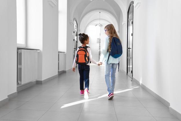 Duas alunas em jeans e tênis com mochilas andando no corredor de luz longa depois das aulas. Foto Premium
