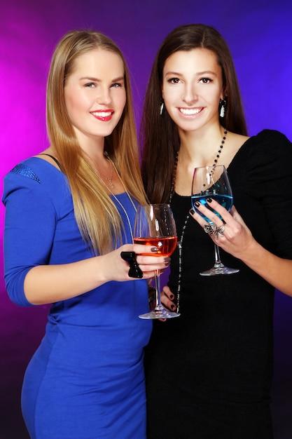 Duas amigas alegres com cocktails coloridos Foto gratuita