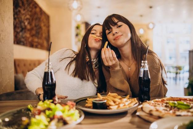 Duas amigas comendo pizza em um café Foto gratuita