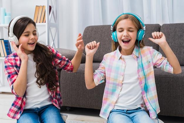 Duas amigas curtindo a música no fone de ouvido em casa Foto gratuita