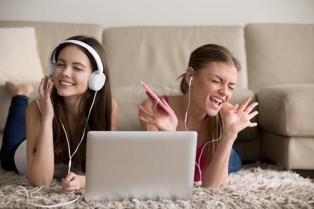 Duas amigas em fones de ouvido se divertindo em casa Foto gratuita