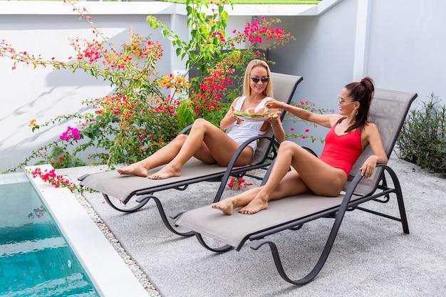 Duas amigas em traje de banho asiáticas e caucasianas na espreguiçadeira à beira da piscina em uma villa com melancia férias em países tropicais frutas frescas Foto gratuita