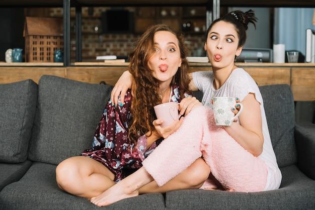 Duas amigas saindo de língua fazendo cara engraçada Foto gratuita