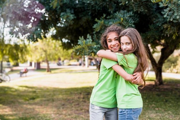 Duas amigas se abraçando no jardim Foto gratuita