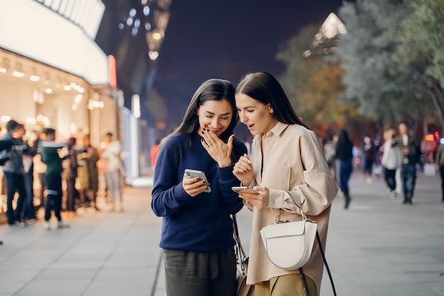 Duas amigas usando o celular enquanto exploram uma nova cidade à noite Foto gratuita