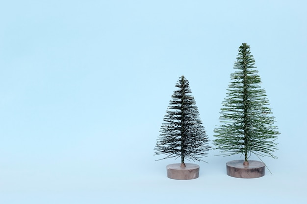 Duas árvores de natal no fundo claro no estilo minimalista. enfeites de natal, ano novo e conceito de inverno. Foto Premium